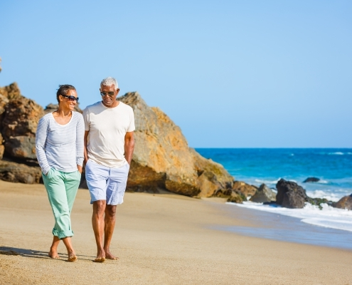 Senior African American couple walking on beach